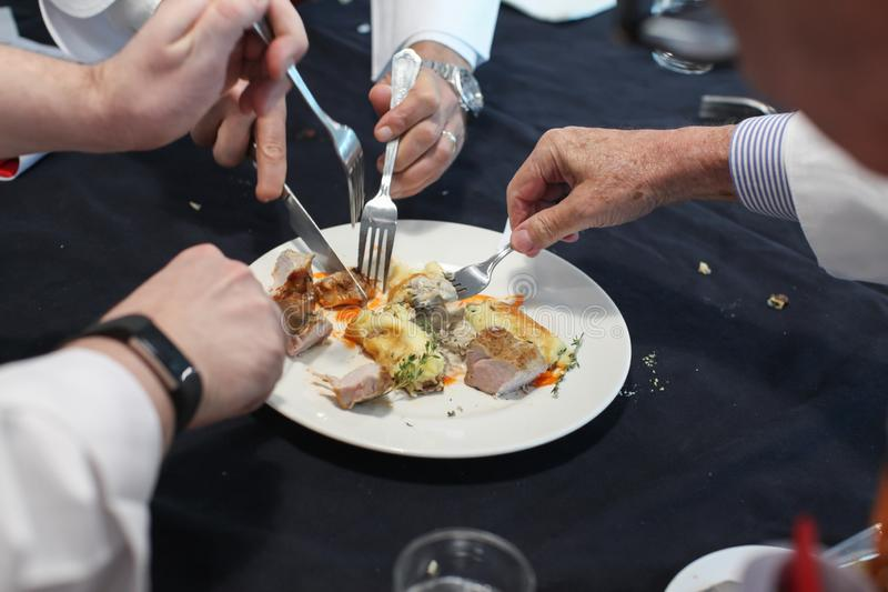 The blurred background of the group of foodies is dividing the food in dish to taste. The blurred background of the group of foodies is dividing the food in the royalty free stock photos