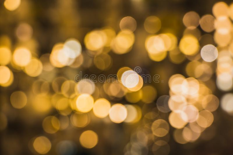 A blurred background with a group of yellow, orange, brown circles from lighted lamps. The abstract beautiful blurred background with a group of multi colored royalty free stock image