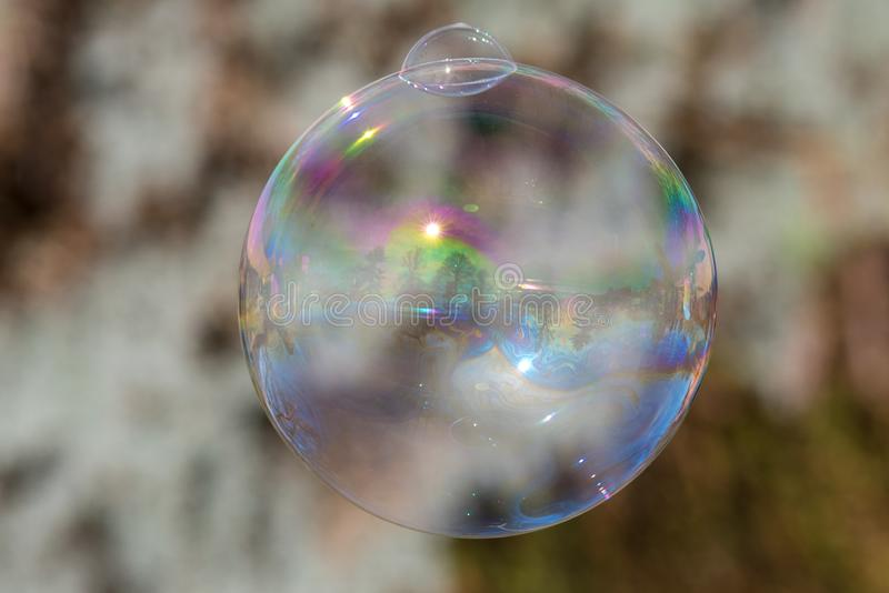 Large bubble with smaller mini version growing from it. Blurred background with large soap bubble in fun and colorful image royalty free stock images