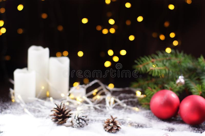 Blurred background for New Year card, dark background with glowing garland, red Christmas balls and white candles on the stock image