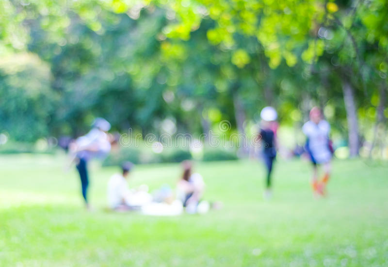 Blurred background of people activities in park with bokeh light. Spring and summer stock image