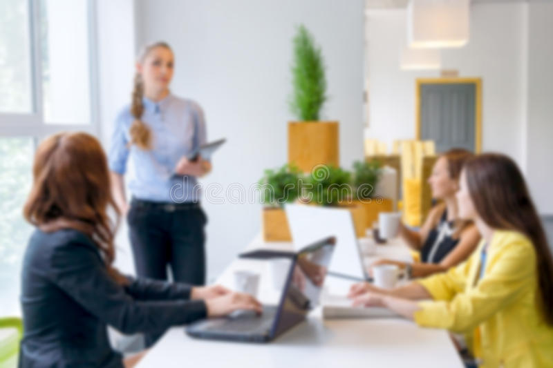 Blurred background. Pretty young business woman giving a presentation in conference or meeting setting. People and royalty free stock images