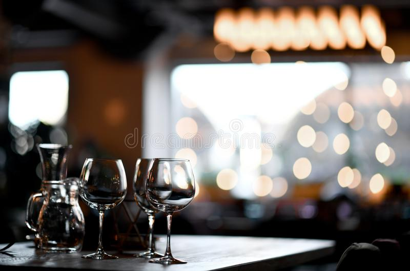 Blurred background in restaurant interior details in blurred bokeh focus on empty wine glasses stock photos