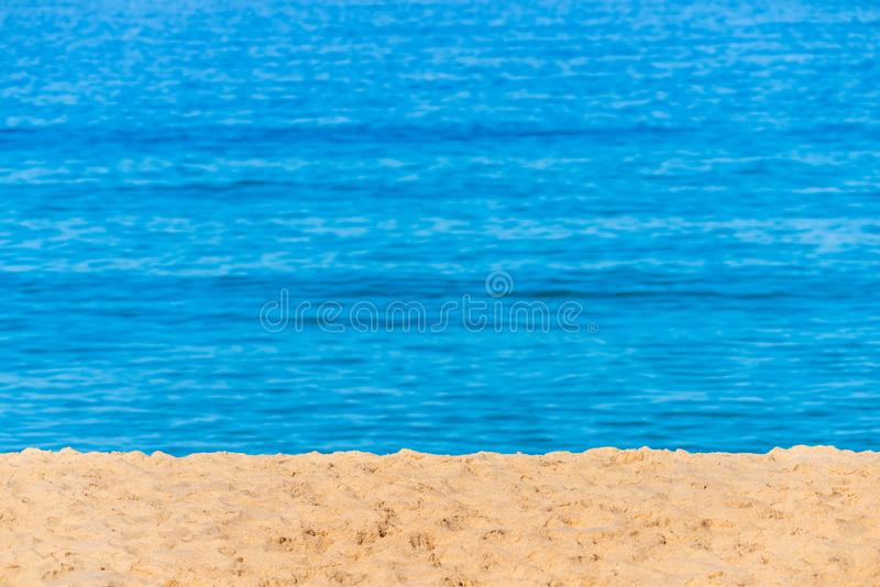 Blurred background sea. Abstract summer background. Glare of the sun against the sea, beautiful bokeh. Yellow sand on the beach stock photography
