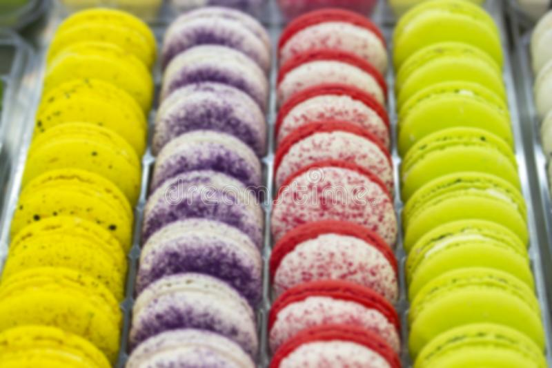 Blurred background showcase pastry shop. Smooth rows of cookies, cakes, yellow red purple white macarons on the counter of stock image