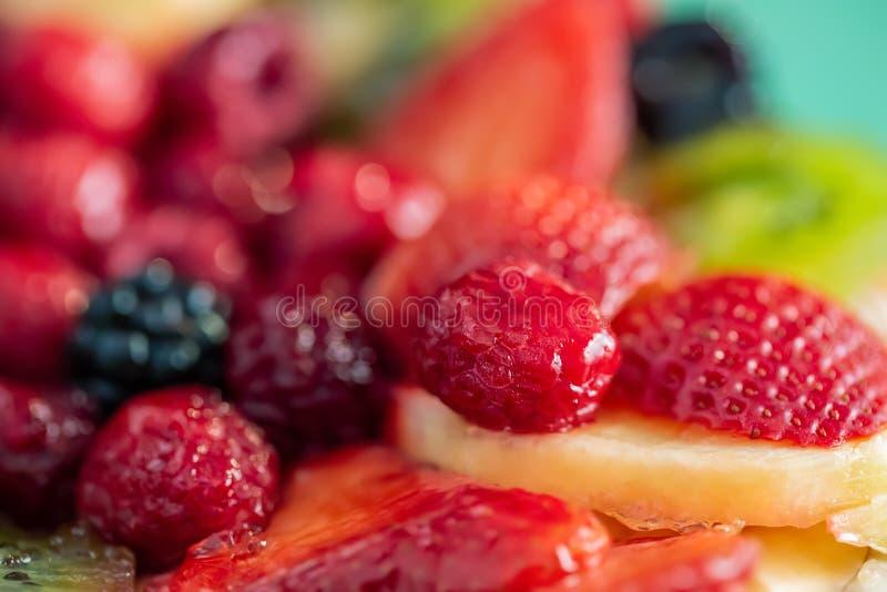 Blurred background of strawberries, kiwi, currants, raspberry, pineapple, blackberry. Delicious dessert. Soft focus. Closeup stock image