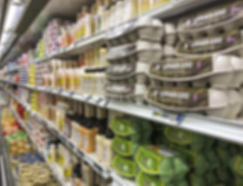 Blurred background with supermarket shelves of dairy products royalty free stock photography