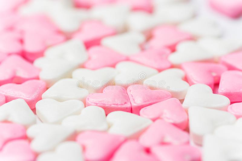 Blurred background for Valentines day charity romantic concept from white and pink sugar candy hearts. Girls baby shower birthday royalty free stock image