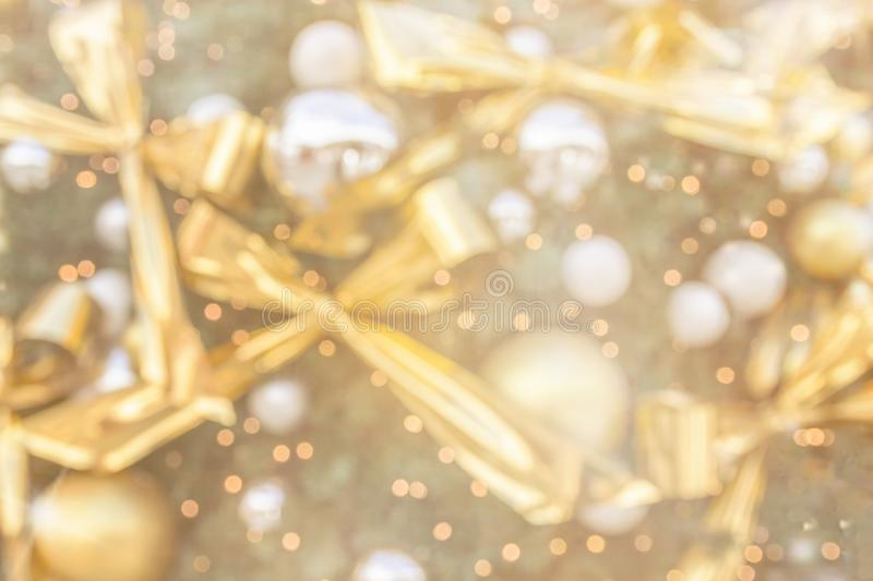 Blurred background for vintage Christmas New Year greeting card poster decorated fir tree golden ornaments balls sparkling garland. Lights warm pastel color stock image