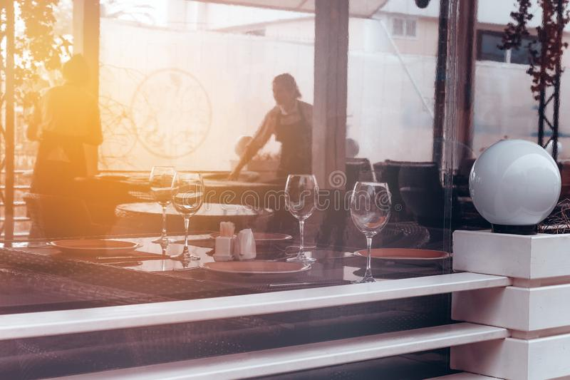 Blurred background   window of the restaurant with wine glasse and waitress. Abstract blurred background   window of the restaurant with wine glasse and waitress stock photos