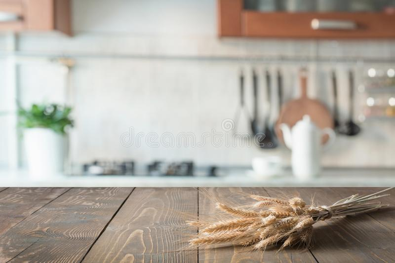 Wooden tabletop with wheat on blur kitchen room background for montage product. stock photography
