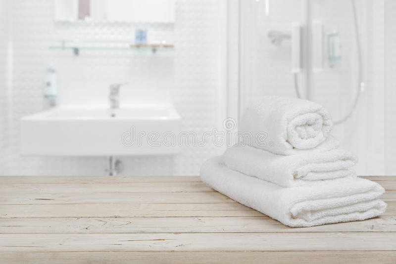 Blurred bathroom interior background and white spa towels on wood stock photography
