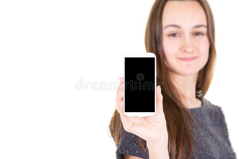 Blurred beautiful attractive pretty youn girl holding smartphone with empty black screen royalty free stock photography