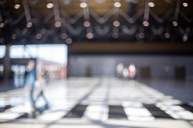 Blurred beautiful bokeh background: blurred people, traveller silhouette is walking in the airport departure hall stock image