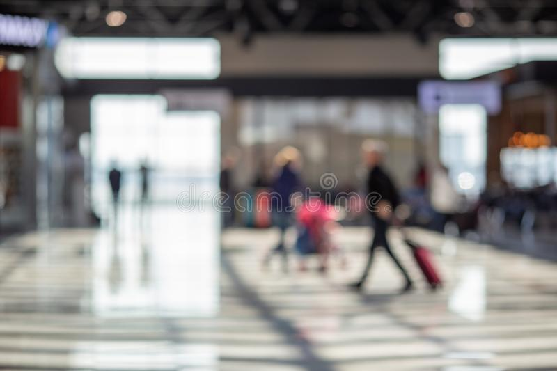 Blurred beautiful bokeh background: blurred people, traveller silhouette is walking in the airport departure hall stock images