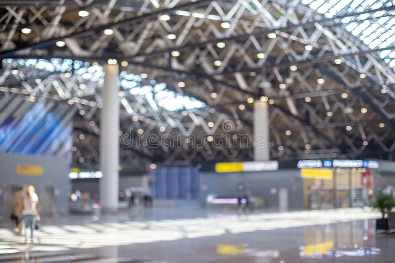Blurred beautiful bokeh background: blurred people, traveller silhouette is walking in the airport departure hall stock photography