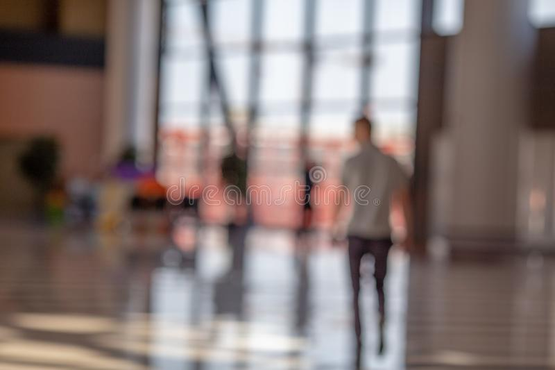 Blurred beautiful bokeh background: blurred people, traveller silhouette is walking in the airport departure hall stock photo