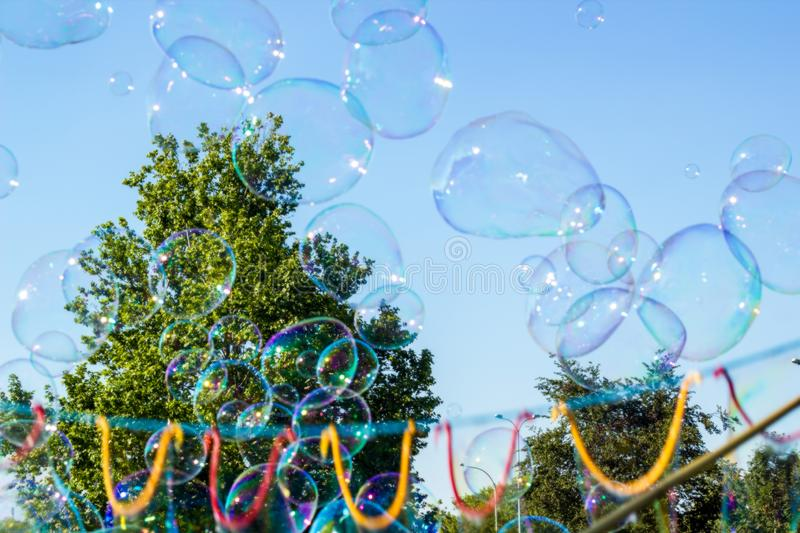 Blurred big soap bubbles flying in blue sky, abstract background. Blurred big soap bubbles flying in air by blue sky, sunny day in city. Blurry abstract summer stock image