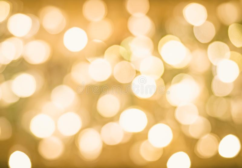 Blurred Bokeh Christmas Glowing Golden Background. Christmas Lights. Gold Holiday New Year Abstract Glitter Defocused royalty free stock photo