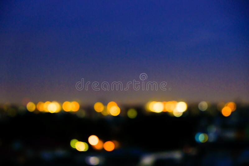 Blurred bokeh city building light sunset with colorful sky cloud. Business background royalty free stock photography