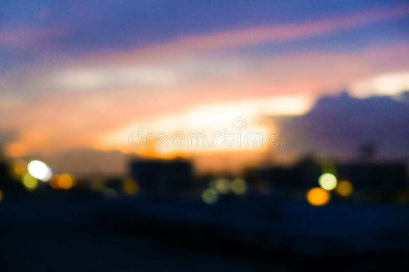 Blurred bokeh city building light sunset with colorful sky cloud. Business background royalty free stock images