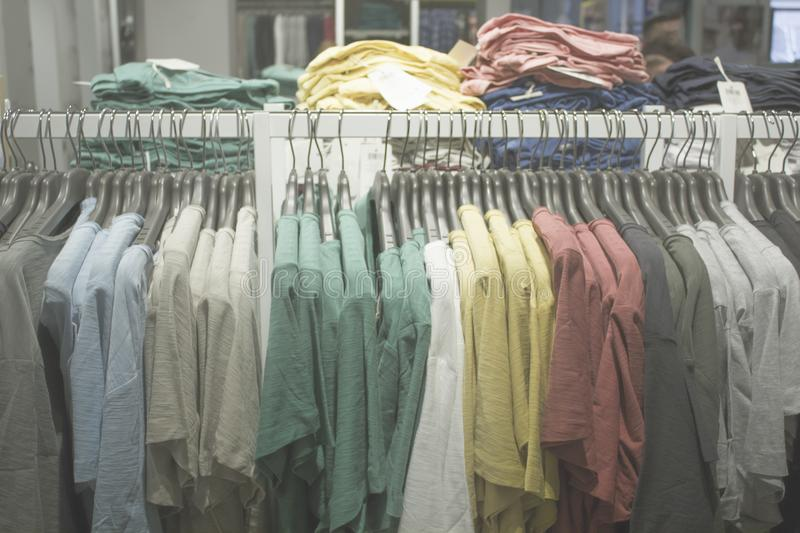 Blurred Bokeh Image of a Retail Clothing Store with hanging apparel for background royalty free stock image