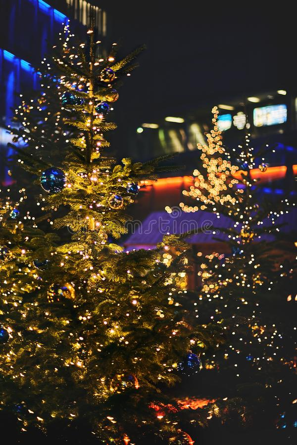 Blurred bokeh with lights .Christmas tree decorated with balls of blue and yellow, garland with warm colored bulbs stock photo