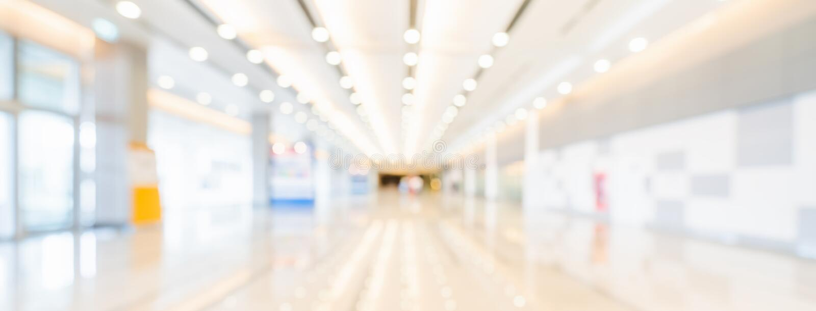 Blurred bokeh panoramic banner background of exhibition hall or convention center hallway. Business trade show event royalty free stock images