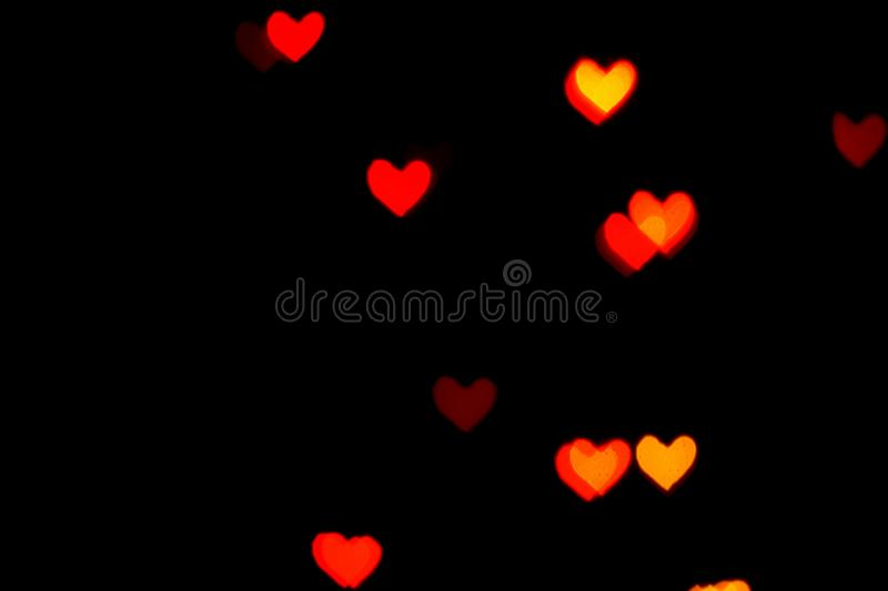 Red blurred lights in the shape of hearts in the dark stock photo