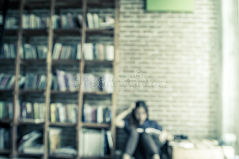 Blurred books on the shelf with people is reading a book. In public library in vintage color tone stock photos