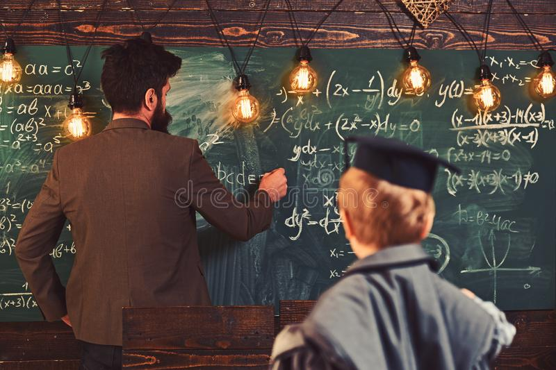 Blurred boy teach man to write on chalkboard. Son and father have school lesson. Parent and child in graduation cap in. Blurred boy teach men to write on stock photography