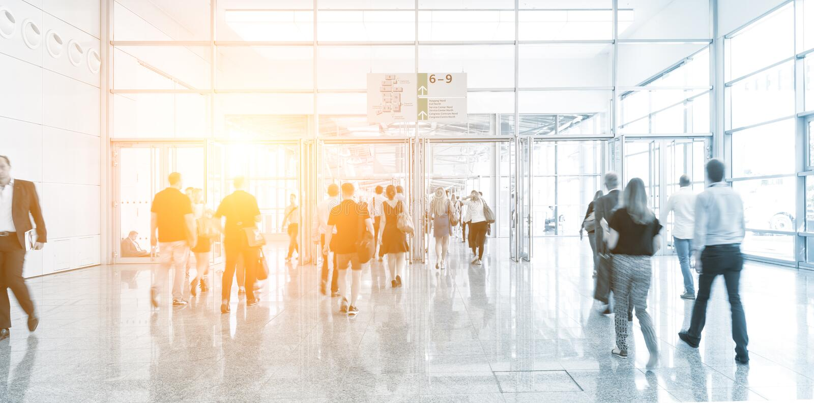 Blurred business people at a trade show floor. Crowd of people rushing in a entrance of a trade show. ideal for websites and magazines layouts royalty free stock images