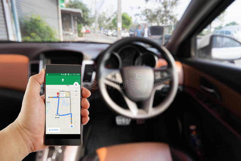 Blurred car interior on the background. Holding black mobile smart phone with map gps navigation application with planned route on the screen. Blurred car stock images