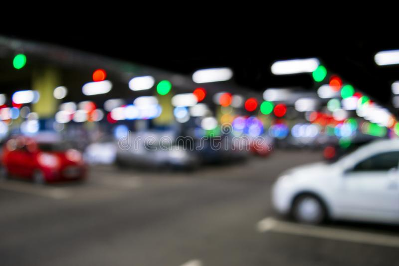 Blurred cars in car parking lot in shopping mall. Bokeh lights background. Abstract blur car parking lot for background. Blurred c stock photography