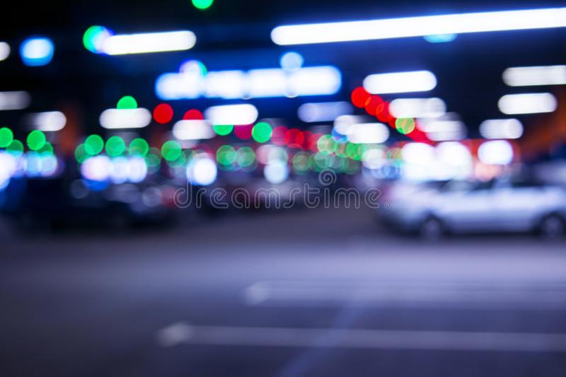 Blurred cars in car parking lot in shopping mall. Bokeh lights background. Abstract blur car parking lot for background. Blurred c royalty free stock photography