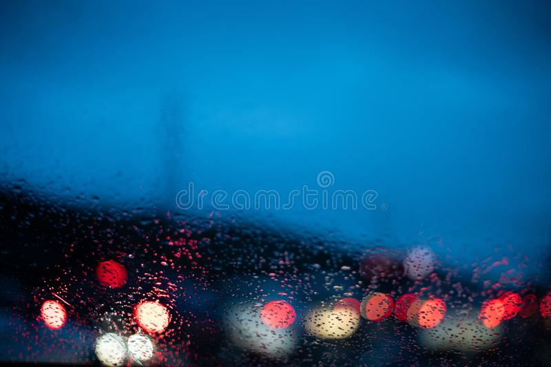 Blurred cars lights from inside a car with drops on the window. With copy space royalty free stock photo