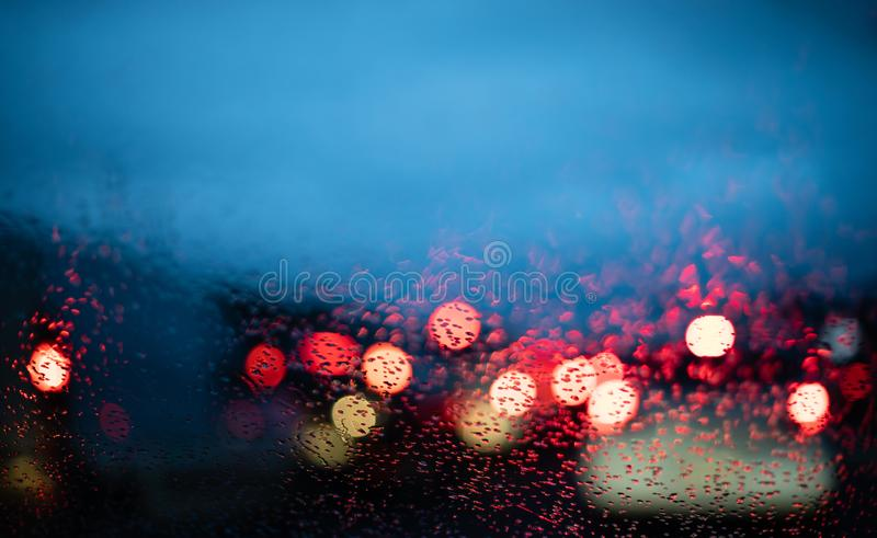 Blurred cars lights from inside a car with drops on the window. With copy space stock photos