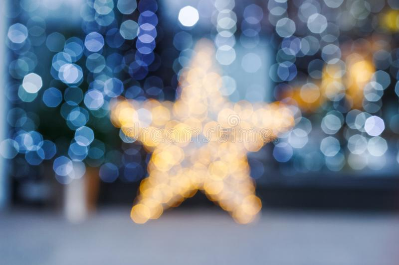 Blurred Christmas background. Gold star and blue blurry lighting royalty free stock images