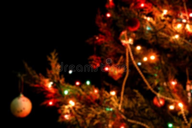 Blurred Christmas tree with Christmas ornaments and bokeh lights on black background. Soft colors. New year concept and background royalty free stock image