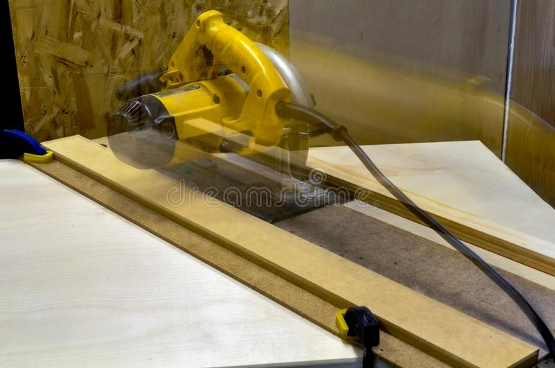 Blurred circular saw in motion on a track. A handy home made DIY jig for the woodworker and carpenter royalty free stock image