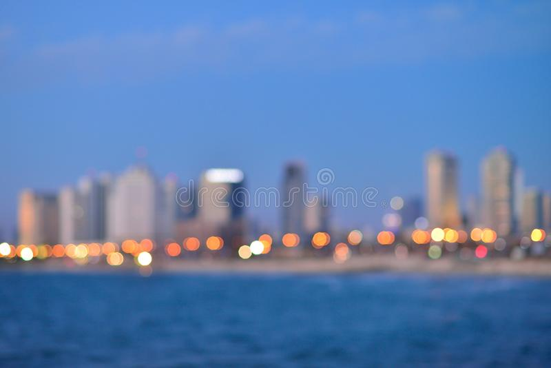 Blurred city lights with bokeh effect reflected on water stock images