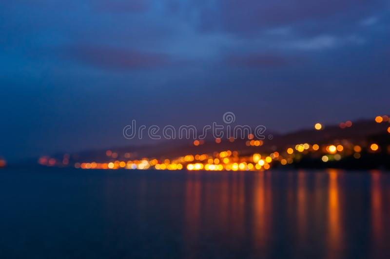 Blurred cityscape with light bokeh and sea. Blurred cityscape with yellow light bokeh and sea royalty free stock images