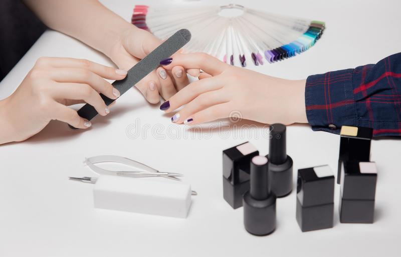 Blurred close-up of black nail polishes, tools. Focus on manicure and grooming woman`s beautiful hands royalty free stock photo
