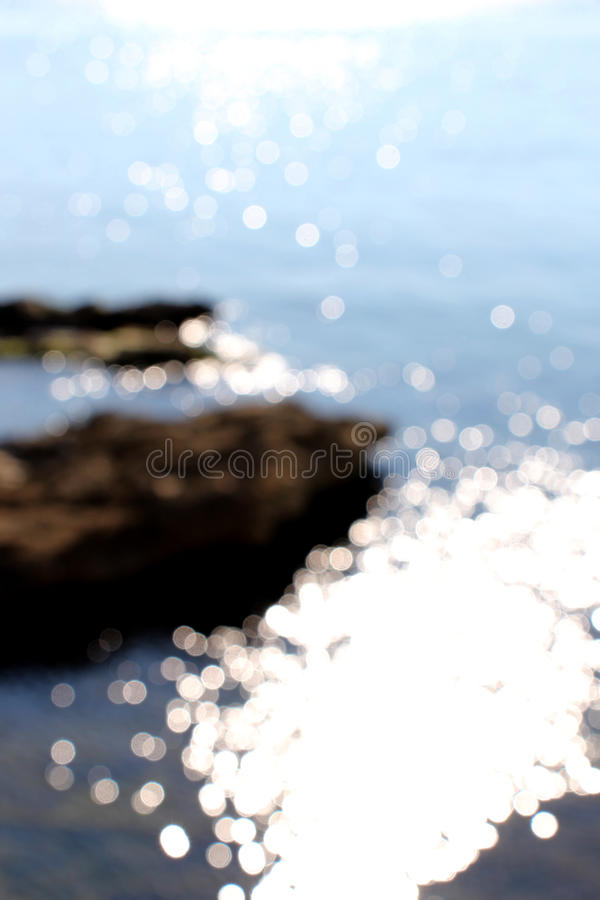 Blurred coast line, with water reflections. A dazzling view of some circles of water reflections, very brilliants, taken in a very sunny day, with the coast line royalty free stock photography