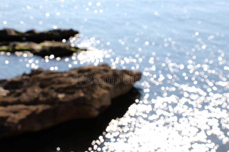 Blurred coast line, with water reflections. A dazzling view of some circles of water reflections, very brilliants, taken in a very sunny day, with the coast line stock photo