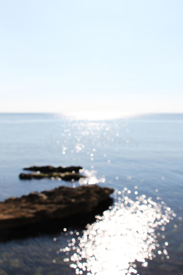 Blurred coast line, with water reflections. A wonderful view of some circles of water reflections, very brilliants, taken in a very sunny day, with the coast royalty free stock photography