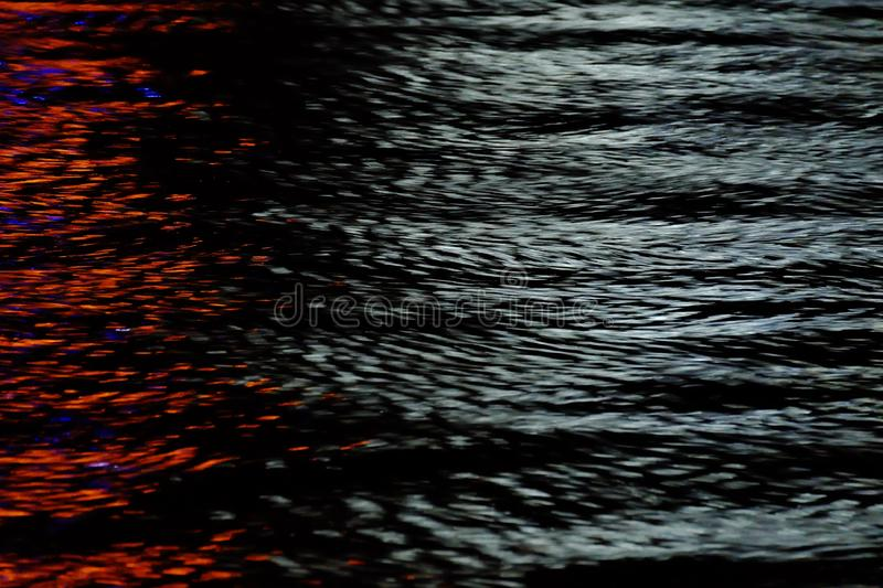 Blurred colorful light on river surface with water waves in the dark night background for backdrop texture stock photography