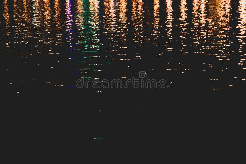 Blurred colorful lights reflect on water surface with ripples in the dark night. abstract texture royalty free stock photo