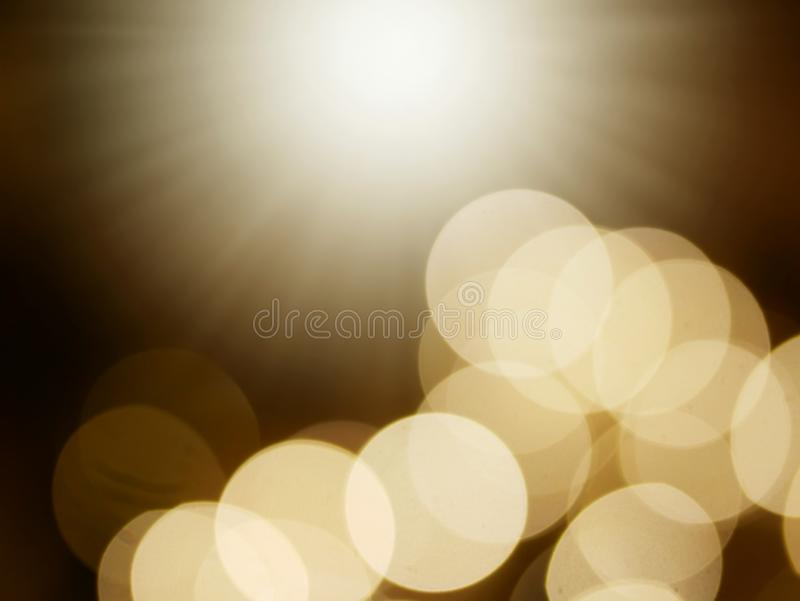 Blurred dark background with yellow bokeh and light source royalty free stock image