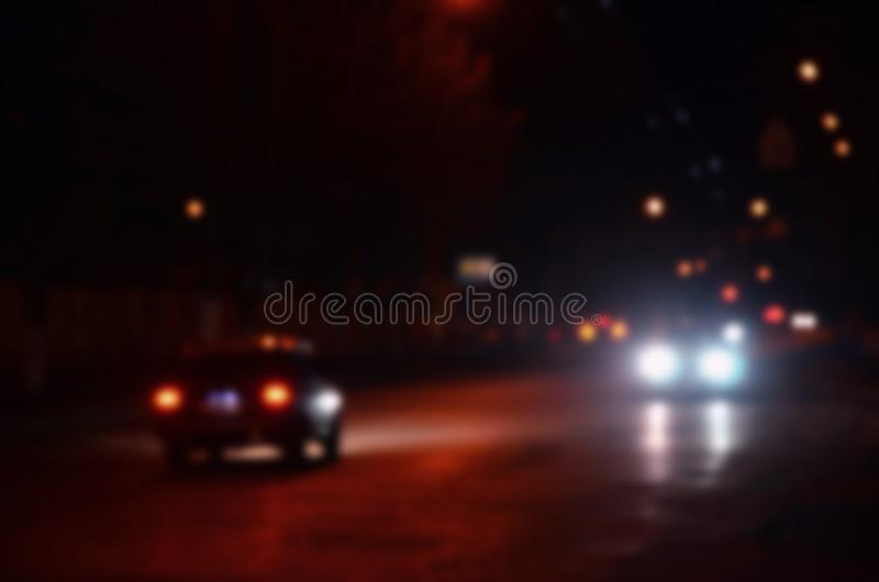 Blurred Defocused Lights of Traffic on a Wet Rainy City Road at Night - Commuting at Rush Hour ConceptnAbstract bokeh from car li. Ght on the traffic road royalty free stock image